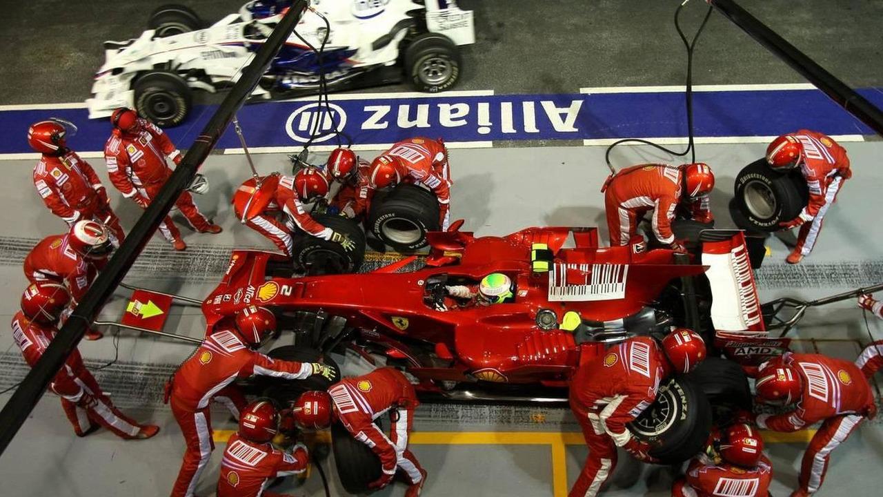 Felipe Massa runs off with the fuel hose attached