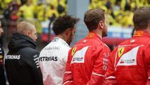 Valtteri Bottas, Mercedes AMG, Lewis Hamilton, Mercedes AMG, Sebastian Vettel, Ferrari, and Kimi Raikkonen, Ferrari, join the other drivers on the grid for the national anthem