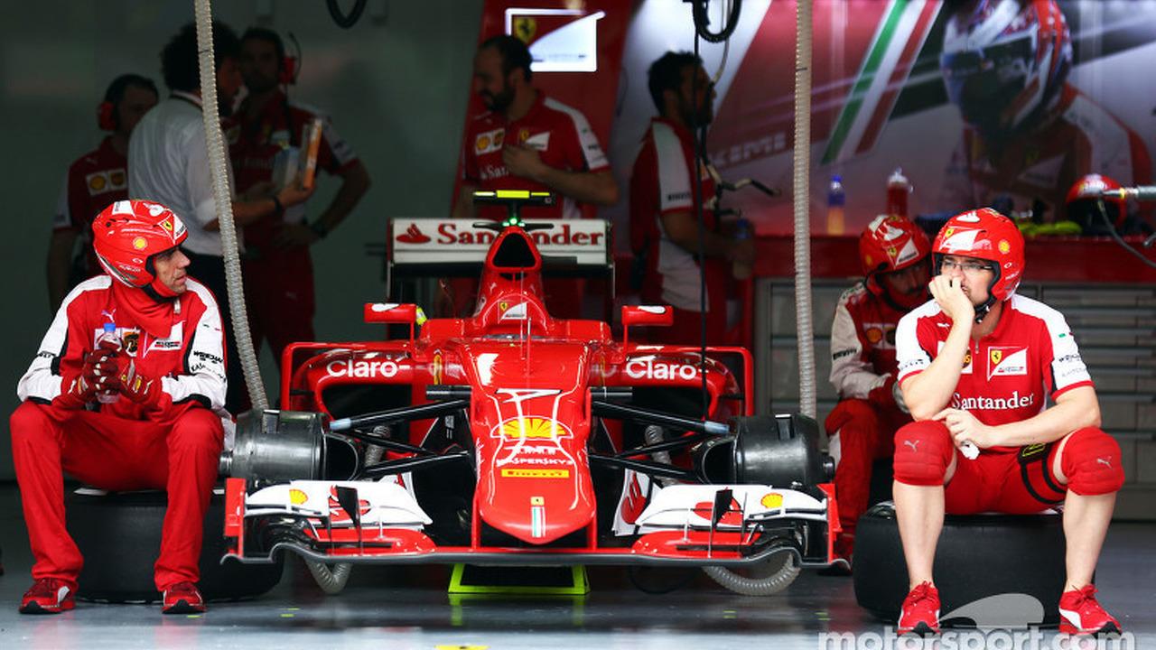 Ferrari mechanics sit by the Ferrari SF15-T of Kimi Raikkonen, Ferrari